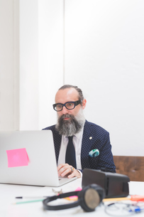 Stylish businessman looking at laptop on office deskの写真素材 [FYI03612826]
