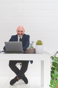 Businessman laughing while looking at laptop on office deskの写真素材 [FYI03612827]