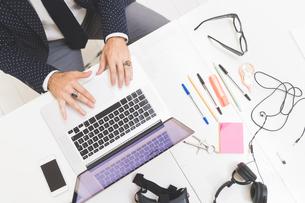 Businessman using laptop on office desk, overhead viewの写真素材 [FYI03612828]
