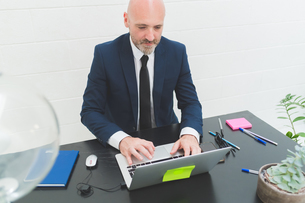 Businessman typing at laptop on office deskの写真素材 [FYI03612829]