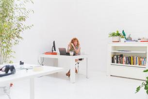 Businesswoman gazing from office deskの写真素材 [FYI03612830]