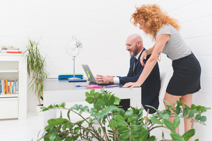 Businesswoman and man looking at laptop on office deskの写真素材 [FYI03612831]