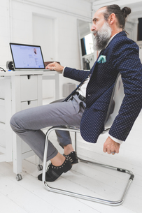 Stylish businessman looking at laptop on office deskの写真素材 [FYI03612834]