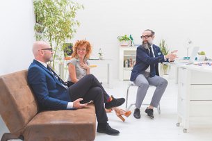 Businessmen and woman having discussion at meeting on office sofaの写真素材 [FYI03612836]