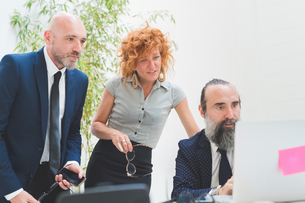 Businesswoman and men looking at laptop on office deskの写真素材 [FYI03612837]