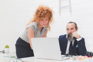 Businesswoman and man looking at laptop on office deskの写真素材 [FYI03612839]