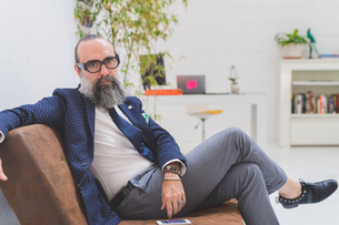 Cool hipster businessman sitting on office sofa, portraitの写真素材 [FYI03612840]