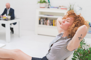 Cool businesswoman with eyes closed and feet up in officeの写真素材 [FYI03612842]