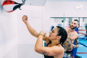 Woman using punch bag in gymの写真素材 [FYI03612896]