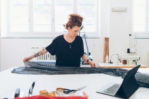 Fashion designer laying out fabric on workbenchの写真素材 [FYI03612922]