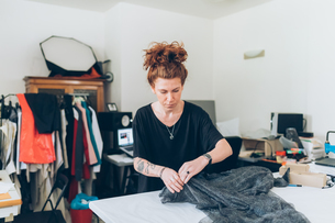 Fashion designer laying out fabric on workbenchの写真素材 [FYI03612926]