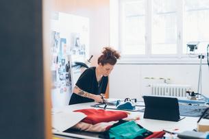 Fashion designer cutting fabric from dressmaker's patternの写真素材 [FYI03612927]