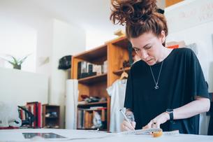 Fashion designer working in her studioの写真素材 [FYI03612930]