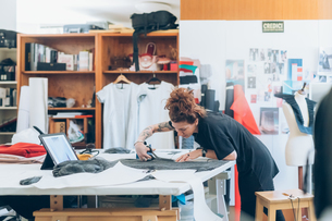 Fashion designer cutting fabric from dressmaker's patternの写真素材 [FYI03612931]