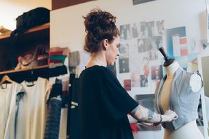 Fashion designer pinning garment onto dressmaker's dummyの写真素材 [FYI03612933]
