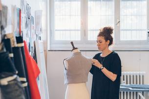 Fashion designer pinning garment onto dressmaker's dummyの写真素材 [FYI03612934]