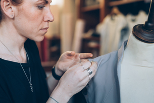 Fashion designer pinning garment onto dressmaker's dummyの写真素材 [FYI03612935]
