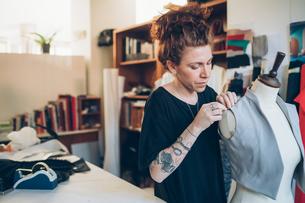 Fashion designer pinning garment onto dressmaker's dummyの写真素材 [FYI03612937]