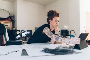 Fashion designer researching using digital tabletの写真素材 [FYI03612938]