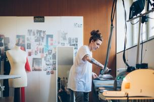 Fashion designer ironing in her work studioの写真素材 [FYI03612943]
