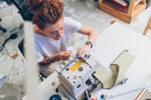 Fashion designer working at sewing machineの写真素材 [FYI03612949]