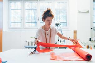 Fashion designer unrolling textile on workbenchの写真素材 [FYI03612965]
