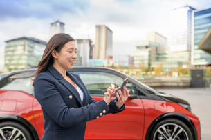 Woman checking electric car charge on mobile phone app, Manchester, UKの写真素材 [FYI03613044]