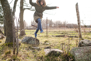 Girl jumping from rock to rock in fieldの写真素材 [FYI03613248]