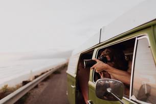 Man on van road trip photographing coast, Ventura, California, USの写真素材 [FYI03613305]