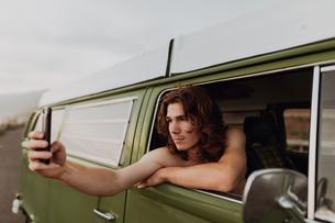 Man on van road trip taking selfie, Ventura, California, USの写真素材 [FYI03613310]