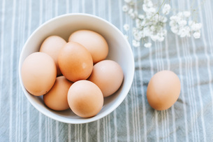 Bowl of eggs on table cloth, overhead still lifeの写真素材 [FYI03613396]