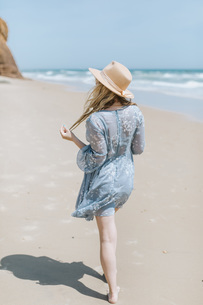 Barefoot young woman strolling on beach, Menemsha, Martha's Vineyard, Massachusetts, USAの写真素材 [FYI03613400]