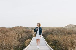 Lone young woman strolling on coastal dune boardwalk,  Menemsha, Martha's Vineyard, Massachusetts, Uの写真素材 [FYI03613416]