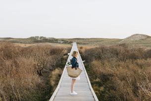 Lone young woman looking out from coastal dune boardwalk,  Menemsha, Martha's Vineyard, Massachusettの写真素材 [FYI03613421]