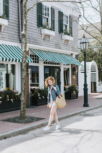 Young woman strolling along street carrying straw bag, Menemsha, Martha's Vineyard, Massachusetts, Uの写真素材 [FYI03613437]
