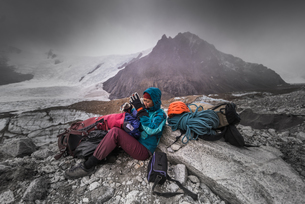 Rock climber by climbing equipment shielding from extreme weather, El Chalt駭, south Patagonia, Argeの写真素材 [FYI03613477]