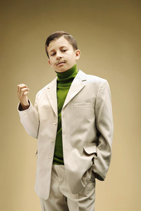 Young boy dressed in beige suit with fake mustacheの写真素材 [FYI03613594]