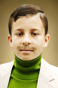 Young boy dressed in beige suit with fake mustacheの写真素材 [FYI03613596]