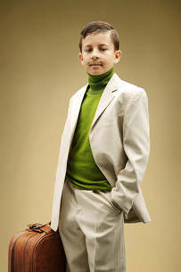 Young boy dressed in beige suit with fake mustacheの写真素材 [FYI03613597]