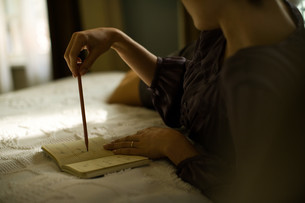 Woman lying on bed in hotel room writing diaryの写真素材 [FYI03613626]