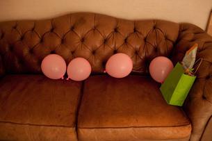 Pink balloons on sofaの写真素材 [FYI03613680]
