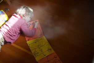 Young boy lying on floor drawingの写真素材 [FYI03613694]