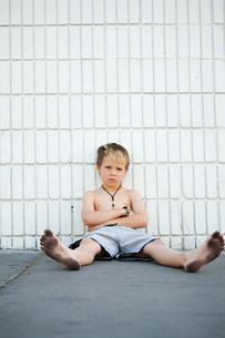 Boy with dirty feet sitting by brick wallの写真素材 [FYI03613925]