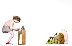 Girl playing miniature piano for teddy bearsの写真素材 [FYI03613943]