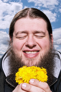 Happy bearded man with yellow flowersの写真素材 [FYI03613964]