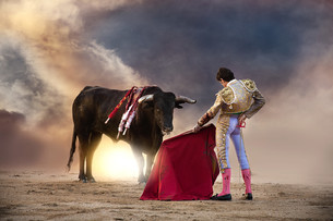 Bullfighter holding red cape with bull, Madridの写真素材 [FYI03613970]