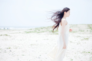 Young woman with long windswept black hair on beachの写真素材 [FYI03614052]