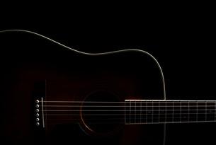 Acoustic guitar against black backgroundの写真素材 [FYI03614130]
