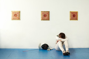 Female fencer sitting against wall with head in handsの写真素材 [FYI03614151]