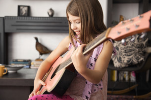 Girl playing acoustic guitar at homeの写真素材 [FYI03614221]